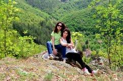 Dos hermanas sonrientes en la montaña con su perro Fotos de archivo libres de regalías