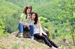 Dos hermanas sonrientes en la montaña con su perro Imagen de archivo