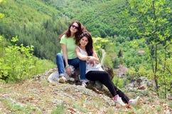 Dos hermanas sonrientes en la montaña con su perro Foto de archivo