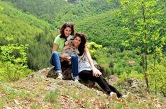 Dos hermanas sonrientes en la montaña con su perro Fotos de archivo