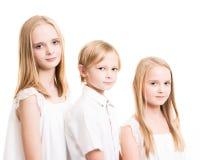 Dos hermanas y su Brother Dressed en blanco en el estudio Foto de archivo