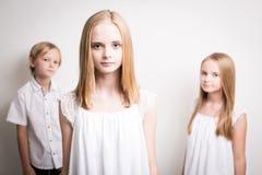 Dos hermanas y su Brother Dressed en blanco en el estudio Imágenes de archivo libres de regalías