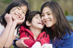 Dos hermanas y su pequeño hermano lisiado Foto de archivo libre de regalías