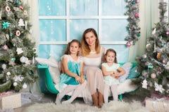 Dos hermanas y una madre joven en decoraciones de una Navidad Fotos de archivo libres de regalías