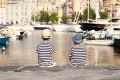 Dos hermanos abrazan y miran las naves, yate en el mar Imagenes de archivo
