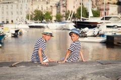 Dos hermanos abrazan y miran las naves, yate en el mar Imagen de archivo libre de regalías