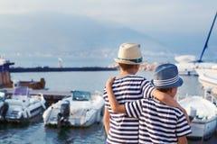 Dos hermanos abrazan y miran las naves, yate en el mar Imágenes de archivo libres de regalías