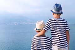 Dos hermanos abrazan y miran las naves, yate en el mar Fotografía de archivo