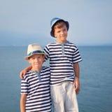 Dos hermanos abrazan y miran las naves, yate en el mar Foto de archivo libre de regalías