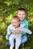 Dos hermanos adorables que se sientan en hierba verde Imagenes de archivo