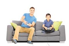 Dos hermanos asentados en un sofá que juega a los videojuegos Foto de archivo libre de regalías