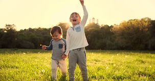 Dos hermanos caminan en el campo en el verano en la puesta del sol que lleva a cabo las manos felices y alegres metrajes
