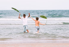 Dos hermanos de un adolescente que juega en el océano, la amistad o Imagenes de archivo