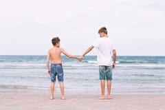 Dos hermanos de un adolescente que juega en el océano, la amistad o Imagen de archivo libre de regalías