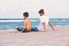Dos hermanos de un adolescente que juega en el océano, la amistad o Fotos de archivo