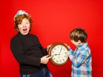 Dos hermanos del rojo-pelo que presentan con el reloj grande Imagen de archivo libre de regalías