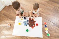 Dos hermanos dibujan las pinturas, sentándose en el piso imagen de archivo