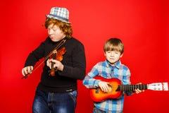 Dos hermanos divertidos del rojo-pelo que juegan música Imagen de archivo