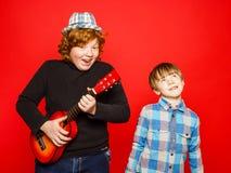 Dos hermanos divertidos del rojo-pelo que juegan música Imágenes de archivo libres de regalías