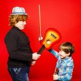 Dos hermanos divertidos del rojo-pelo que juegan música Foto de archivo