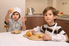 Dos hermanos en cocina Imagenes de archivo