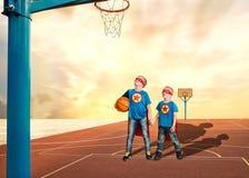 Dos hermanos en el traje de super héroes juegan a baloncesto imagen de archivo libre de regalías