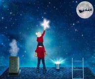 Dos hermanos en la situación de la noche de la Navidad en el tejado de la casa y recoger las estrellas del cielo en un cubo Feliz imagen de archivo libre de regalías
