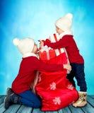 Dos hermanos encontraron un bolso con los regalos de Santa Claus ¡Feliz Navidad y buenas fiestas! imágenes de archivo libres de regalías
