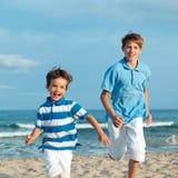 Dos hermanos están corriendo en la playa Imagen de archivo libre de regalías