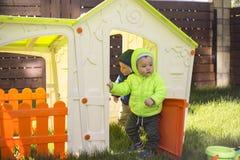 Dos hermanos gemelos juegan y se divierten en la casa grande del juguete del patio fotos de archivo