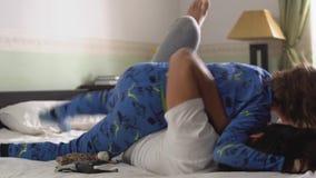 Dos hermanos juegan en la cama, una más vieja lucha del hermano y fijan a su hermano menor, son felices y risa hermanos almacen de metraje de vídeo