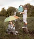 Dos hermanos juegan en la lluvia al aire libre retra corrigen fotografía de archivo libre de regalías