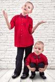 Dos hermanos juegan y se divierten, hacen a amigos, pasan el tiempo junto Llevan la misma ropa de moda, camisas fotografía de archivo libre de regalías