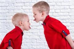 Dos hermanos juegan y se divierten, pasan el tiempo junto Los niños se vistieron en la misma ropa de moda, camisas fotos de archivo