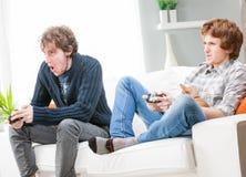 Dos hermanos o amigos que juegan a los videojuegos Imagen de archivo