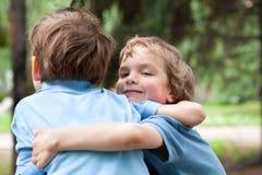 Dos hermanos que abrazan en parque Imágenes de archivo libres de regalías