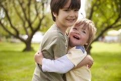 Dos hermanos que abrazan en parque junto imágenes de archivo libres de regalías