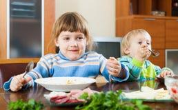 Dos hermanos que comen junto Imagen de archivo