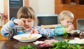 Dos hermanos que comen la comida junta Imagenes de archivo