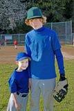 Dos hermanos que desgastan los uniformes del béisbol. Fotografía de archivo