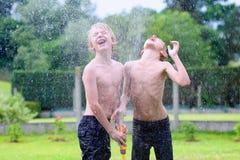 Dos hermanos que juegan con agua riegan en el jardín Fotografía de archivo libre de regalías