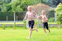 Dos hermanos que juegan con agua riegan en el jardín Fotos de archivo