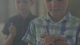 Dos hermanos que juegan con el fuego en el cuarto ahumado oscuro Un muchacho encendió el encendedor en el fondo que otro encendió metrajes