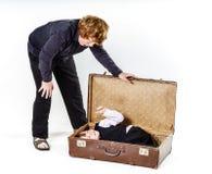 Dos hermanos que juegan con la maleta retra Imágenes de archivo libres de regalías