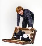 Dos hermanos que juegan con la maleta retra Imagen de archivo
