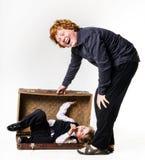 Dos hermanos que juegan con la maleta retra Fotos de archivo libres de regalías