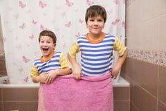 Dos hermanos que juegan con la toalla rosada en el cuarto de baño Imágenes de archivo libres de regalías