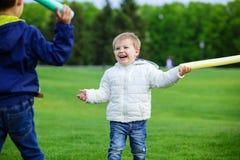 Dos hermanos que juegan con las espadas y la risa del juguete Foto de archivo