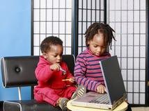 Dos hermanos que juegan con una PC Imagenes de archivo