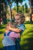 Dos hermanos que juegan en el césped en el parque Fotos de archivo libres de regalías